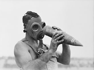 Australia and weapons of mass destruction - An observer examining an unexploded 25 pound gas shell following a trial of gas weapons at Singleton, New South Wales in 1943.