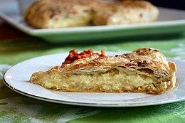 Gibanica single slice with full pie in background.jpg