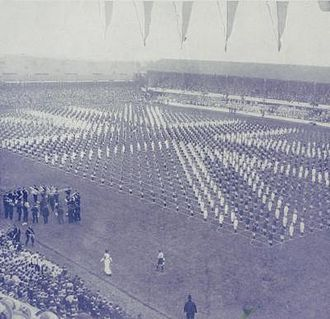 Goodison Park - Men in dark blue and white suits stand across the pitch in formation, creating the image of a Union Flag. 80,000 people attended Goodison Park to see King George V.