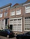 foto van Huis met witgepleisterde lijstgevel, schilddak. Nog geheel woonhuis