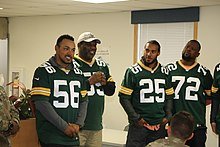 Grant standing with other Packers alumni, who are wearing their jerseys, talking with soldiers.