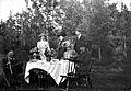 Gruppbild av ett sällskap kring ett dukat bord i trädgården - Nordiska Museet - NMA.0056419.jpg