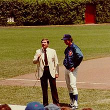Two men standing on a grass-and-dirt field; the man on the right is wearing a blazer and slacks, while the man on the left—the subject of the image—is wearing white pinstriped baseball pants, a blue nylon warm-up jacket, and a blue baseball cap.
