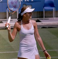 Daniela Hantuchova in a white dress and white cap, holding her racket aloft, holding a ball in her left hand