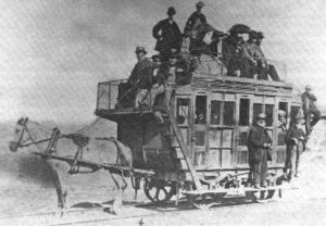 Train surfing - An early horse-hauled rail car with passengers on its roof and foot boards