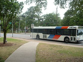 Transportation in Houston - A METRO bus driving through the University of Houston campus on Cullen Boulevard.