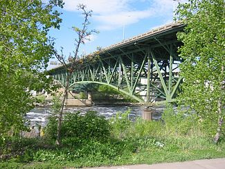 picture of the bridge painted green and surrounded by green foliage seen from the Mississippi bank
