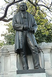 A bronze metal sculpture of a nineteenth century man wearing a long jacket or coat, trousers, waistcoat, with draughtsman's tools in his hands
