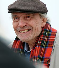 Man in a hat and red scarf smiling