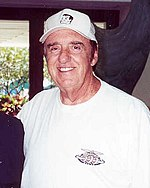 Man in his late 70s, smiling and wearing a white t-shirt and baseball cap.
