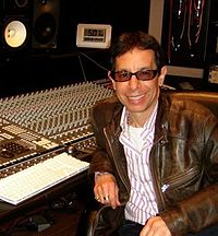A man with short brown hair is seen looking in the direction of the camera. The photo was taken in a recording studio.