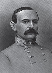 A man with receding dark hair and a full, dark mustache wearing a high-collared military jacket