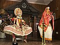 Kathakali artists representing Deva (green make up, sitting) and woman (yellow, standing), Nataraja image behind on stage background.jpg