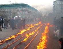Várias velas estão dispostas em forma de cruz em uma estrada, enquanto uma multidão de pessoas observa.