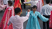 Women dressed in traditional outfits dance with men on the street.