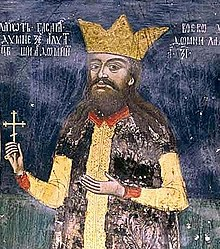 A bearded middle-aged man wearing a crown and holding a cross in his right hand