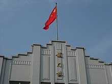 Picture of Longmen Building and Chinese Flag.