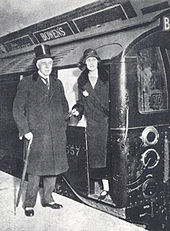 A smartly dressed middle aged gentleman in top hat, velvet-trimmed coat and stripped trousers with spats and rolled umbrella stands next to the open door of the driver's cab of an underground railway train in a station tunnel. A young woman (his daughter) in a long coat and cloche hat stands in the cab doorway.