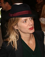 Laurent wearing a black hat and a black top looking away from the camera.