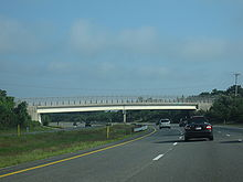 Ground-level view of a busy, six-lane divided freeway; a large overpass bridge is visible in the distance.