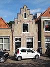 foto van Huis met trapgevel met geprofileerde dekplaten en gewijzigde topafdekking. Ontlastingsbogen van vroegere vensters. Topanker