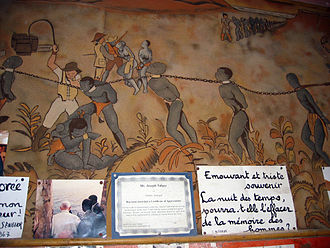 House of Slaves - A wall in the Museum: a mural depicting slaves being herded in the African bush by Europeans, a photo of Joseph Ndiaye with Pope John Paul II, a certificate from a US travel agency, and an aphorism -- one of many that cover the walls -- by Ndiaye. This one reads Moving and sad memory / Night of times / How will it be erased from the memory of Men?.