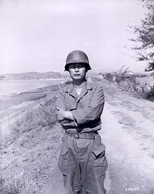 An Asian man in a military uniform in an outdoor setting