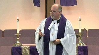 Pastor - A Methodist pastor wearing a cassock, vested with a surplice and stole, with preaching bands attached to his clerical collar