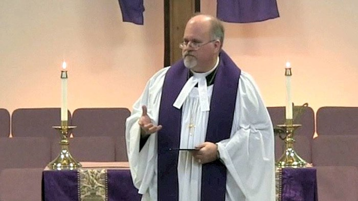 A Methodist pastor wearing a cassock, vested with a surplice and stole, with preaching bands attached to his clerical collar MethodistPastorvestedwithpreachingbands.jpg