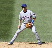 "Baseball player in an athletic stance. He is wearing a blue baseball cap inscribed with a ""T"", and his jersey reads ""TEXAS"" across the front."
