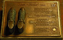 Bronzed shoes on a plaque with text describing Bird's basketball accomplishments