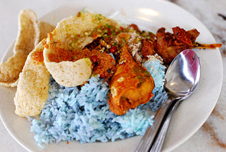 Nasi kerabu - Nasi kerabu served with various herbs, fish meat-stuffed pepper, salted egg, fried fish, keropok and marinated chicken
