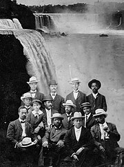 A dozen African American men seated with Niagara Falls in the background