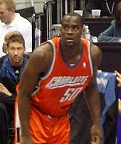 A black person wearing an orange-color jersey stands in front of the spectators