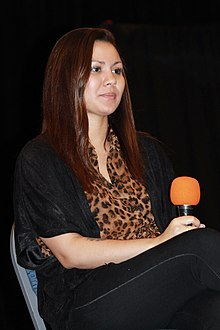 A woman with black hair is seated at a table.