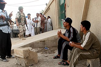 Operation Alljah - An Iraqi policeman talks with two Iraqi civilians as they wait in line to receive new identification cards at a police precinct in Fallujah on 30 June 2007. As part of Operation Alljah, Marines and Iraqi Security Forces sectioned the city into precincts and set up operational stations where Iraqi civilians come in to receive identification cards, food, reimbursements and a chance to join the neighborhood watch program.