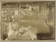 Old damaged and faded monochrome photograph of a woman wearing a pith helmet, long-sleeved and -skirted dress and apron. She is sitting beside a bed, over which hangs a religious picture and behind which is a wall made of reeds.