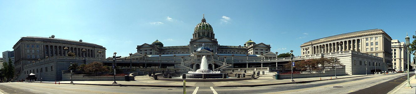 A large plaza with a fountain in front of staircases leading t0 the second level of the plaza. The entire plaza is situated in front of and below a large, domed building. Two large rectangualar buildings the flank the plaza on either side.