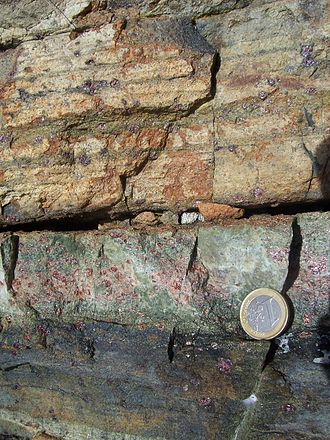 Flow banding - Flow banding at the rim of a peridotite intrusion. Dark and green pyroxenite bands at the bottom represent the melt, brownish lherzolite bands at the top the solid phase. Near Midsund, Norway, 1 euro coin for scale.