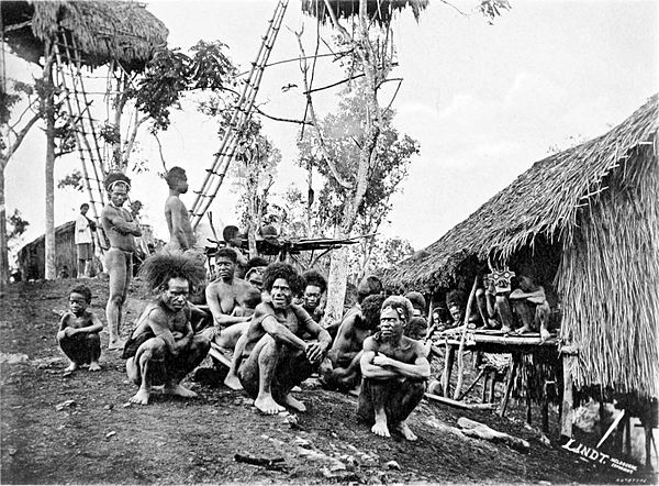 Black and white photograph of men crouching on the ground, next to a hut and trees.