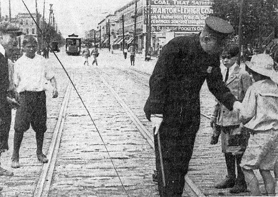 Policeman keeps children away from a fallen electrical wire in Brooklyn (1908)