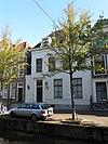 foto van Pand van parterre en verdieping met hoog, omlopend schilddak, waarin twee dakvensters met vleugelstukken