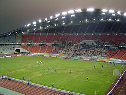 A stadium with green field for football, an athletic track, sitting area and floodlights; a football match is in progress