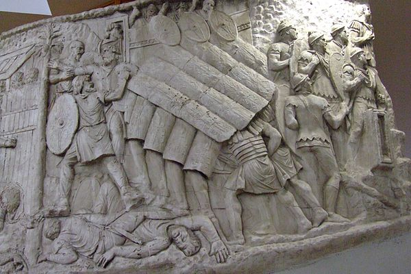 The testudo performed during a siege, as shown on Trajan's Column. There are faint eagle-wing and thunderbolt motifs on the scuta. Roman turtle formation on trajan column.jpg