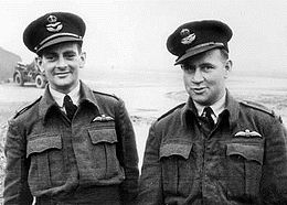 Informal half portrait of two men in dark military uniforms, with peaked caps