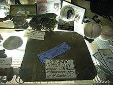 Ein Tisch in einem Antiquitätengeschäft mit vielen verschiedenen Gegenständen, dabei eine rechteckige Kupferplatte