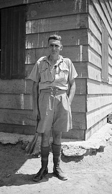 A man, John Hinton, dressed in tropical/desert military uniform and standing outside a hut