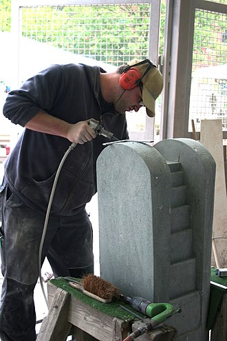 Stonemasonry - Stonemason working on a fountain with pneumatic tools
