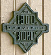 """A building with a plaque reading """"1900 Storm Survivor"""", with the year 2000 at the top and 1900 again at the bottom"""