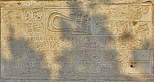 Photo of a stone slab with Arabic lettering, and a Sultan's tughra in the upper middle